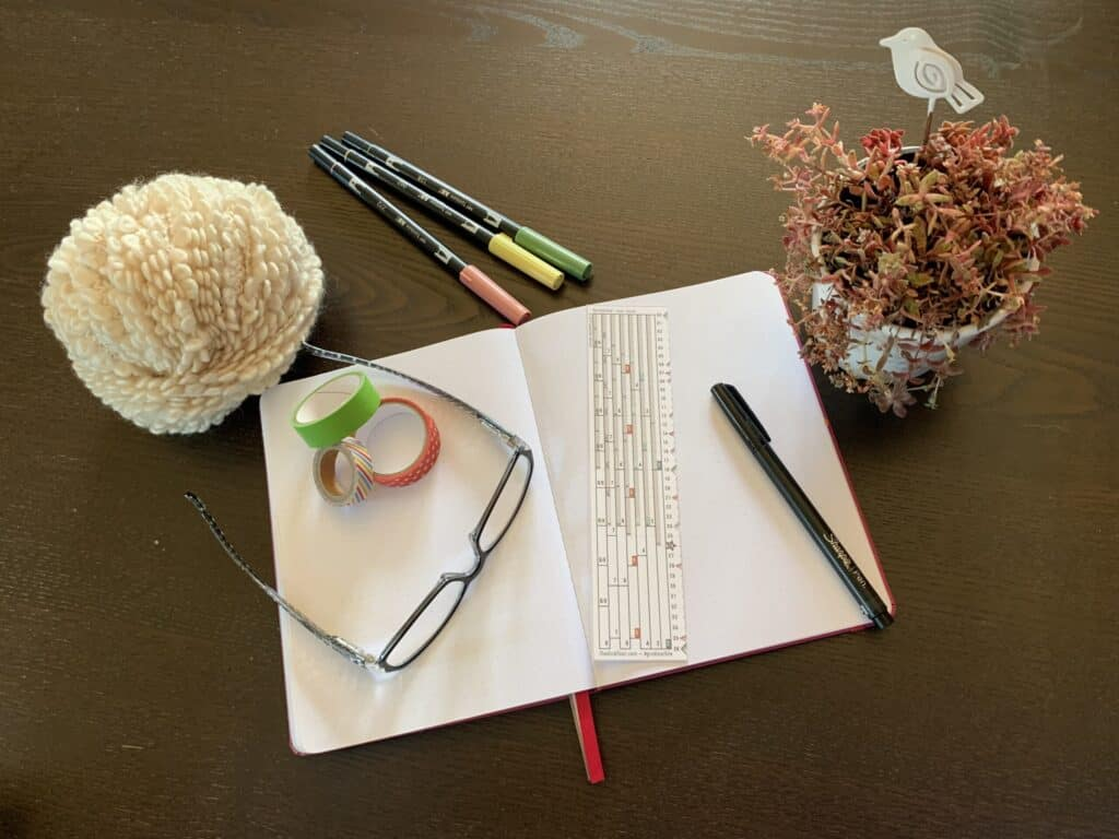 lifestyle photo with The Grid Tool, a journal, and planning accessories